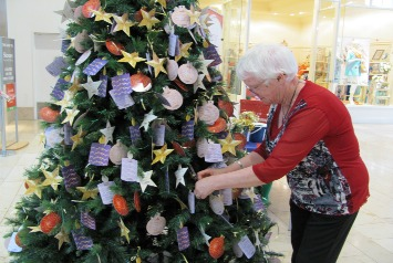 Farmers-Shop:/Footer pages/Charity/Hospice/Hospice Tree of Remembrance/Hospice volunteer Joy placing her message on the tree.jpg